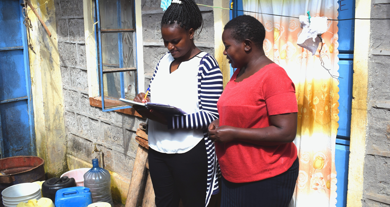 A water service provider marketer gets customer feedback from a residential caretaker. Photo credit: Rose Odengo, WASH-FIN
