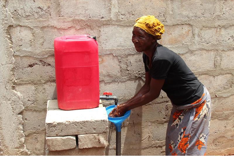 A women washes her hands with a Generation One handwashing station in Benin. Photo credit: Sanitation Service Delivery (SSD)
