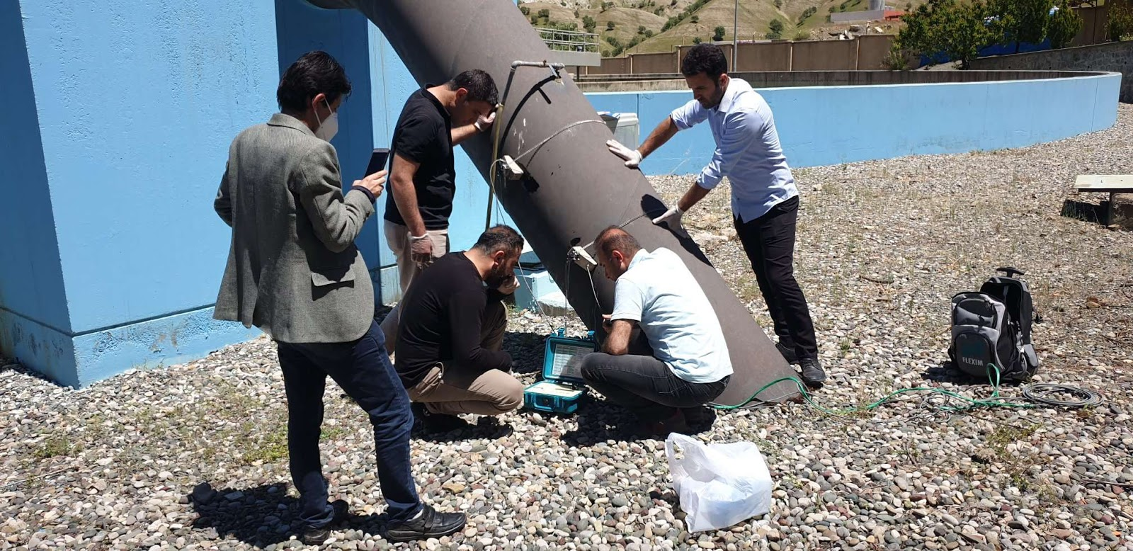 Staff of the Soran Water Directorate use ultrasonic flowmeters to measure the water flow through a main distribution pipe. Photo credit: WADA Tajdid Project