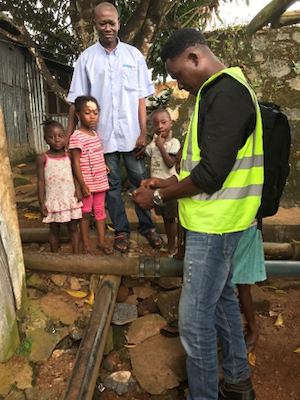 A family looks on as technician Dennis Koroma maps water pipes in Freetown, Sierra Leone. Waterborne diseases are a pressing problem, exacerbated by poor infrastructure, including broken pipes. MCC's investments support the Government of Sierra Leone in its efforts to strengthen Freetown's water utility.