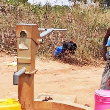 A woman collects water in Zambézia Province, Mozambique. Photo credit: Forcier Consulting.