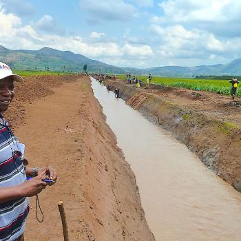In the Democratic Republic of Congo, Dieudonné Mbuka looks on as community members build a channel for water, so the surrounding land can be drained and used for farming. Photo Credit: Marisa Traniello/USAID