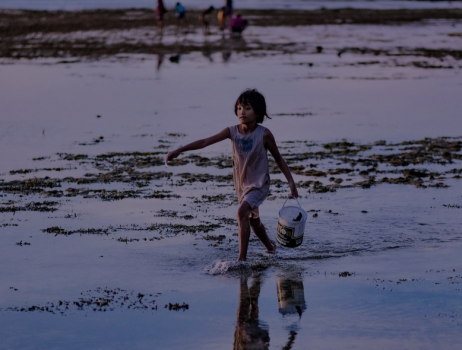 Girl with a bucket on the beach. Photo Credit: Water for Women Fund