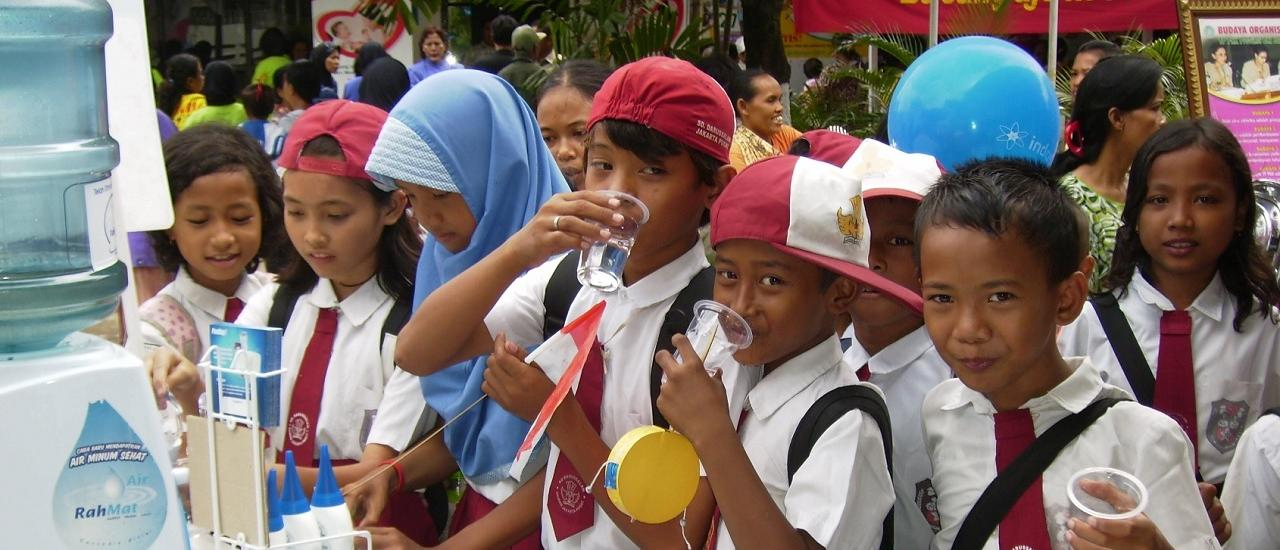Students enjoying purified drinking water at a demonstration in Indonesia. Photo Credit: Institute for Public Health and Water Research