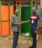 In Abidjan, Cote d'Ivoire, a landlord received the key to a new nine-block latrine for his compound. Photo credit: PSI/USAID SSD Project